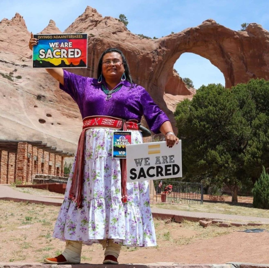 "Mattee Jim stands in front of a canyon of rock, earth, and trees. She wears a rich purple shirt and a white skirt adorned with beaded belts. She holds two signs that read: ""We are sacred."""