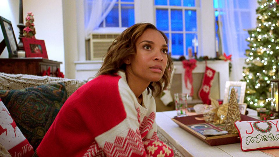a woman in a red christmas sweater leans over a table covered with christmas decorations with a shocked and bereft look on her face