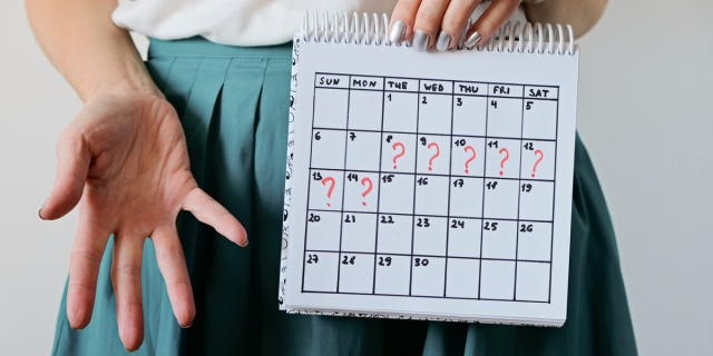 A person in a white shirt and green skirt holds up a calendar. Seven of the dates are marked with red question marks.