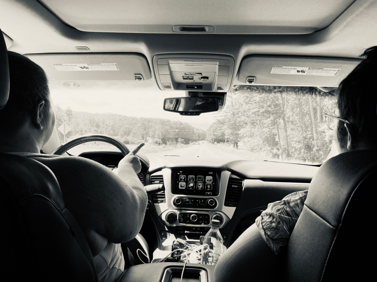 shot of the interior of a car from the backseat toward the windshield. two people are visible in the front seats and the person in the driver's seat is turning the steering wheel