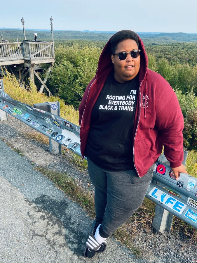 """the author, a fat, Black person leans against the rail on the side of a mountain-side road beside a canyon. they're wearing a red hoodie with the hood up and sunglasses, and their shirt reads """"I'm rooting for everyone Black & trans"""""""