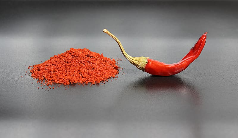 a mound of red chilli powder next to a whole red chilli