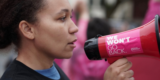 A woman with a serious expression holds a megaphone to her mouth with a sticker on it that reads WE WON'T GO BACK; behind her, a blurred crowd like a protest or audience is suggested.