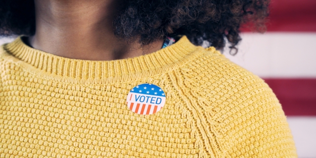 "A closeup of an ""I Voted"" sticker on a bright yellow sweater being worn by a Black woman with shoulder-length natural hair"