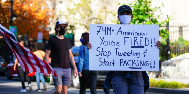 A masked person in a baseball cap holds up a sign that reads 74 million Americans: you're fired! Stop tweeting and start packing!