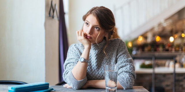 A thin white woman in a baggy sweater stares into space, looking bored, at a café table with a glass of water in front of her