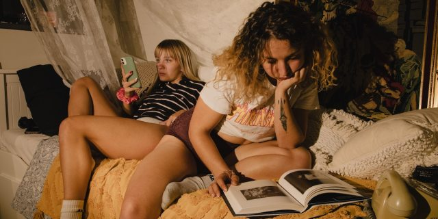 Two women are lounging in a cozy indoor space covered in blanket and pillows with a warm yellow light as if by a flashlight at night, one person reading from their phone screen and one hunched over reading from a hardback book