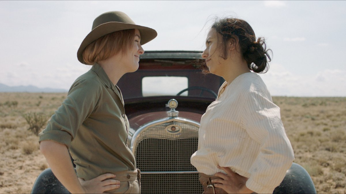 two women face each other beside a car in the dessert, hands on hips, still from sister aimee