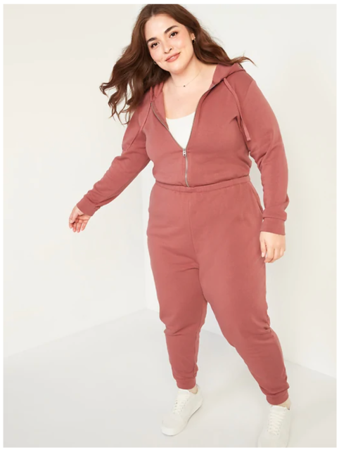 A smiling plus size model poses in a dusty rose zip up sweatsuit