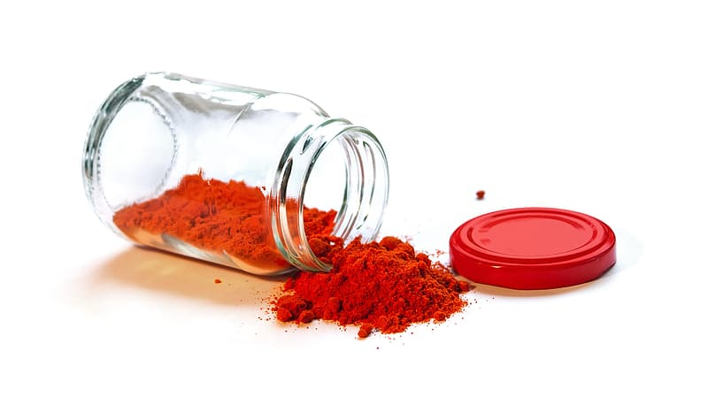 A clear glass jar full of bright red smoked paprika that has fallen on its side so the contents are spilling out