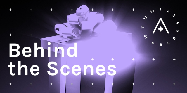 Image reads: Behind the Scenes. A wrapped gift box, lavender against a black background, has a wild, glowing energy coming out of it. The A+ logo is in the upper right.