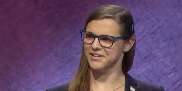 Kate Freeman, a winning contestant on Jeopardy, with thick dark blue glasses and long brown hair swept behind her ear. She is against a purple background.