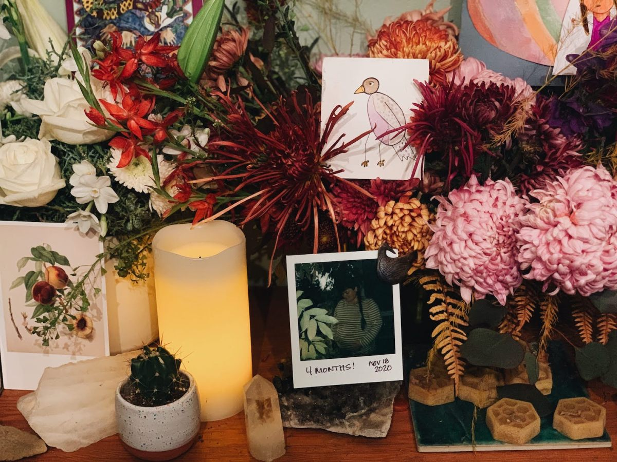 a grief altar filled with flowers, a candle, a drawing of a tiny bird, and a polaroid of a pregnant woman captioned 4 months!