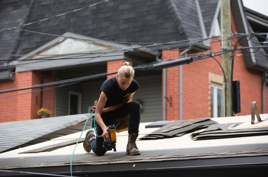A scene from Below Her Mouth where Erika Linder is knelt on a roof with a power tool