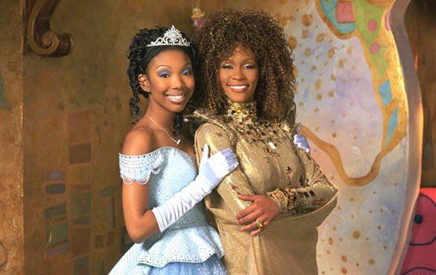 """Still from Roger and Hammersteins 1997 """"Cinderella"""". shows the two stars, Brandy and Whitney Houston, Brandy is wearing a pal blue ball gown and tiara and Whitney Houston is wearing a gold gown."""