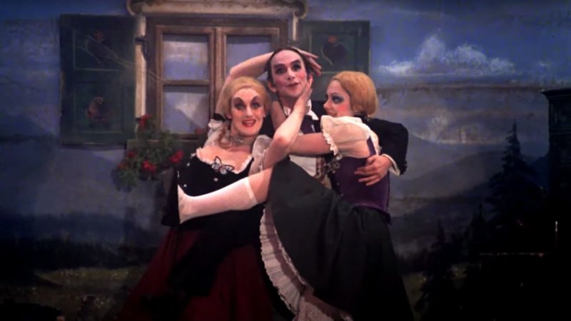 Queer women musicals got a boost in 1972 when Grey's Emcee playfully described his throuple with two gay ladies.