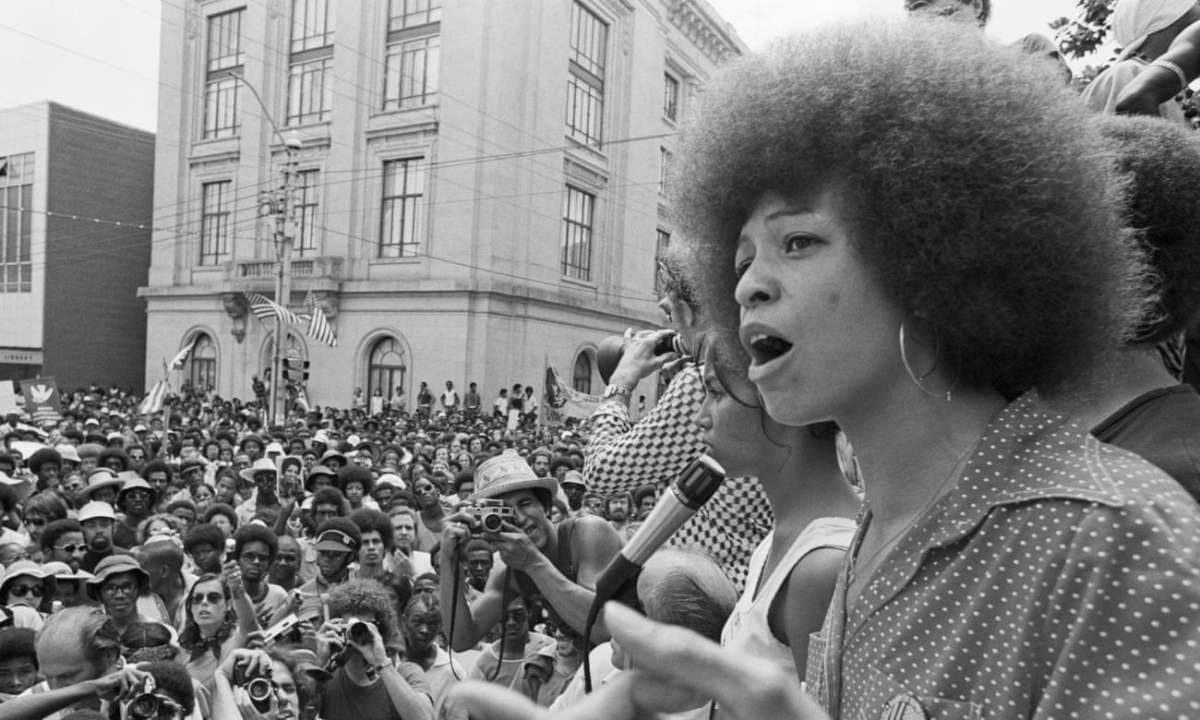 Angela Davis speaking into a microphone in front of a large crowd.
