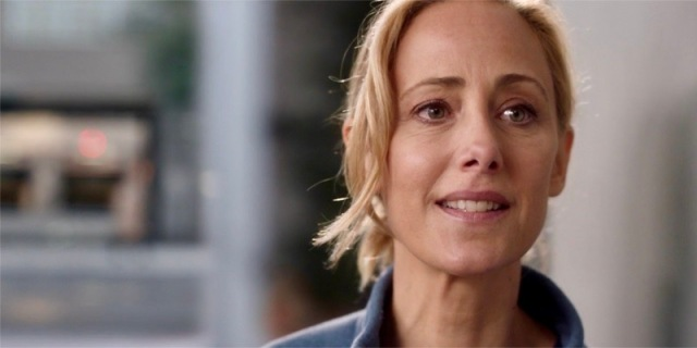 A close up still of Dr. Teddy Altman of Grey's Anatomy nervously smiling at the camera, eyes full of both fear and hope.