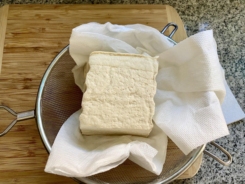 tofu dans une passoire sur des serviettes en papier