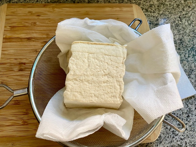 tofu in a strainer on top of paper towels
