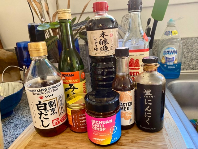 a line up of sauces in jars and bottles: dashi, mirin, chili powder, chili crisp, soy sauce, fish sauce, sesame oil, garlic vinegar