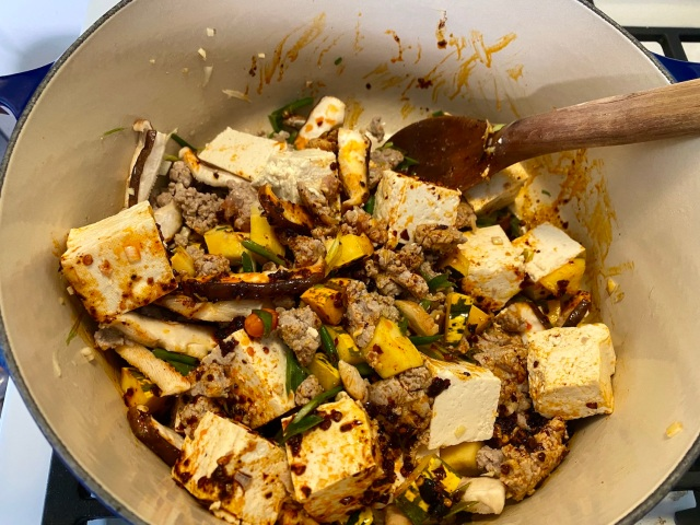 mapo tofu in the making! pot with tofu chunks, pork, squash, shiitakes and chilies