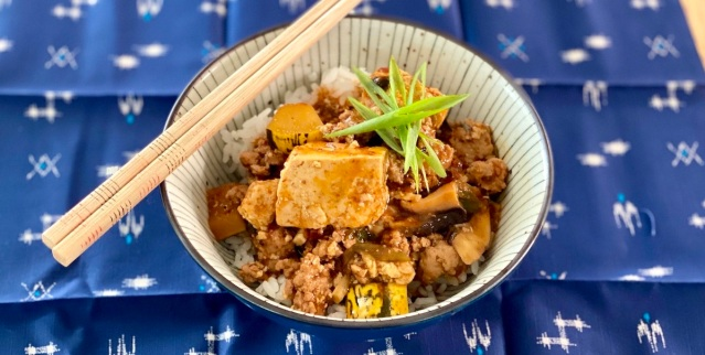 a bowl of mapo tofu over rice topped with a star of sliced scallions. chopsticks rest on the left side of the bowl and the bowl in on a blue woven cloth.