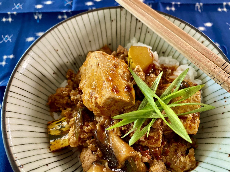 Gros plan d'un bol de tofu mapo sur du riz avec une étoile d'oignons verts en tranches sur le dessus