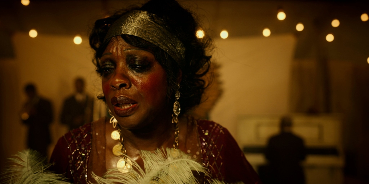 Viola Davis as Ma Rainey, in a gold headdress and a feather boa on stage.