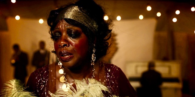 "Viola Davis as Ma Rainey, in a gold headdress and a feather boa on stage. This is a still from Netflix's ""Ma Rainey's Black Bottom"" the latest entry into a queer history of the Blues legend."