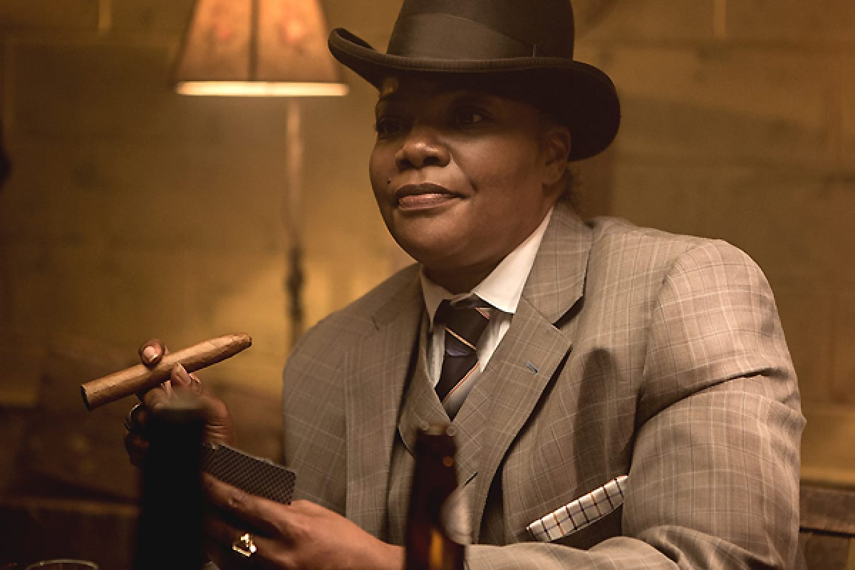 """Mo'Nique in a three-piece suit and fedora, smoking a cigar, in Dee Rees' """"Bessie"""" (2015). This depiction of one within a long history of showcasing Ma Rainey as a queer legend."""
