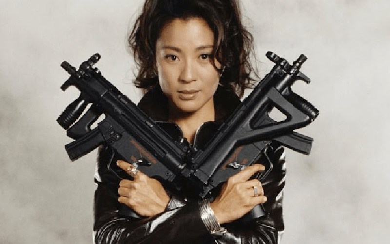 Michelle Yeoh in a leather jumpsuit holding two large guns crossed against her chest.