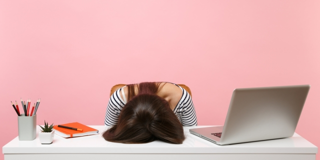 A woman with long, brown hair rests her face on her desk in front of a pink background.
