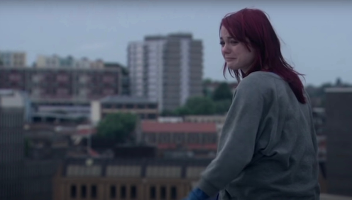 A scene from Skins where Emily Fitch sits on a concrete roof, looking upset with the Bristol skyline behind her