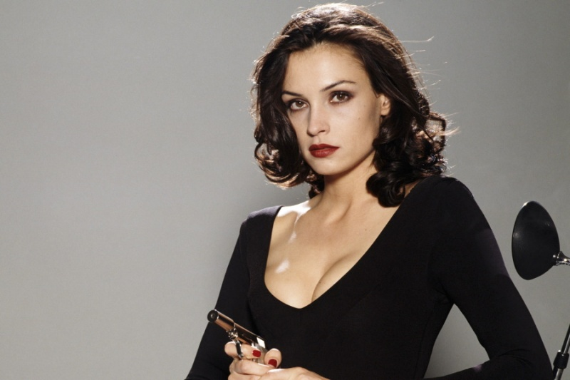 A brunette in a sleek, low-cut black top holds a small shiny pistol. She has dark blood red lipstick.