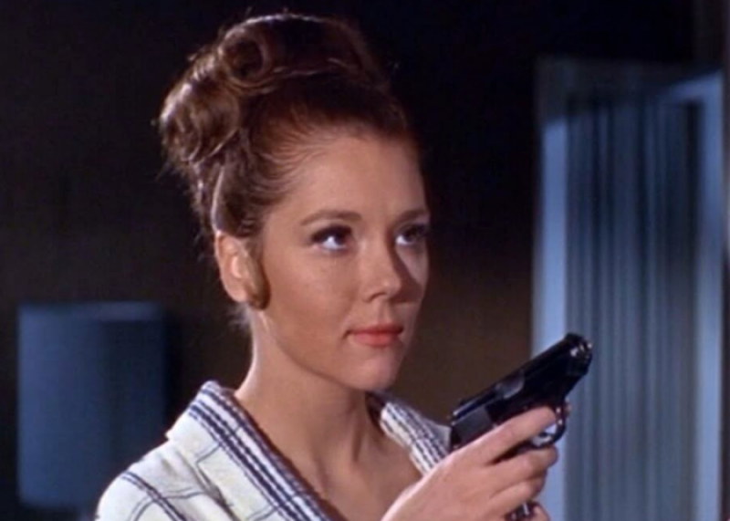 A brunette in a 1960s style updo holds a small pistol while wearing a silk robe.