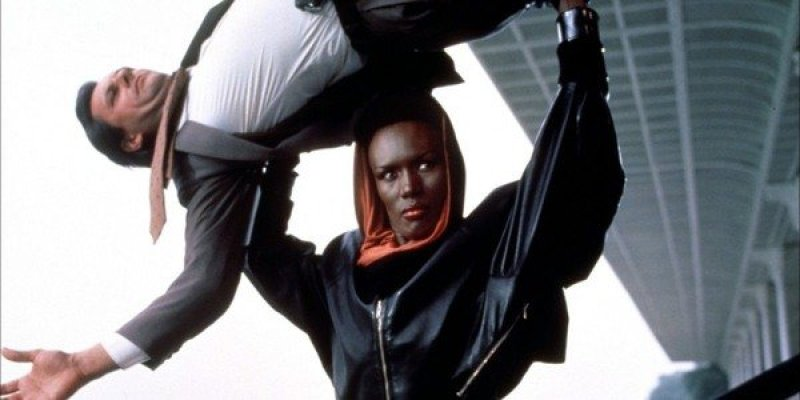 Grace Jones flipping a man over her head while wearing a black and red hoodie
