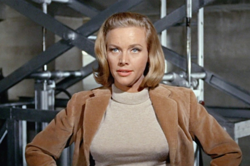 A blonde woman with a bob haircut stands with her hands on hips in a camel colored blazer.