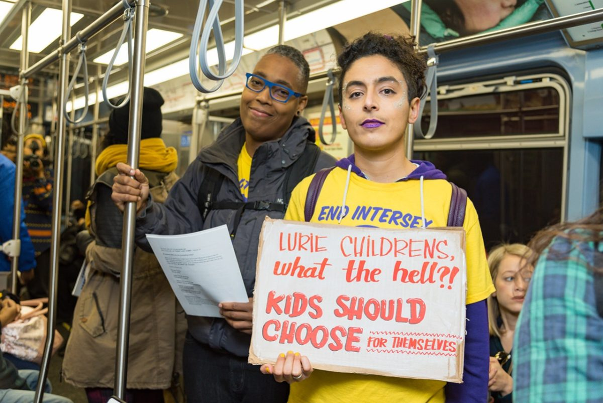 Sean Saifa Wall (left) and Pidgeon Pagonis taking over a public train to protest against intersex surgeries at Lurie Children's Hospital in 2018. Sean Saifa has dark brown skin, short curly hair, and wears glasses. Pidgeon has light skin, wavy hair, and has on purple lipstick.