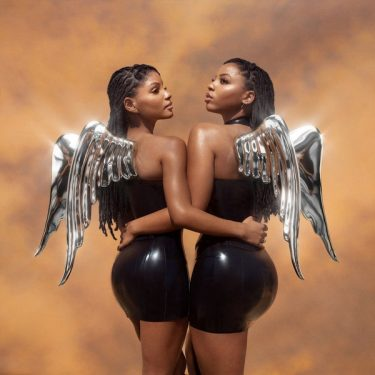 Images shows the cover of Chloe x Halle's album, Ungodly Hour. Both people are in black latex dresses with silver angel wings coming out of their backs. Their hair is loc'd as they look into the distance.