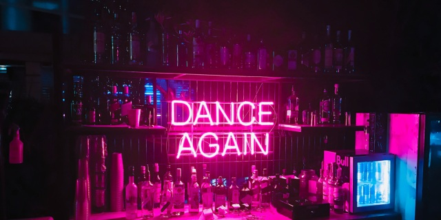 "A neon pink sign says ""Dance Again"" against a bar wall with empty bottle everywhere."
