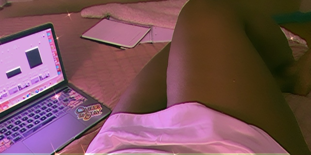 photo of shelli in a bed surrounded by a computer, notebooks and a calender. The photo shows her legs and a white slip.