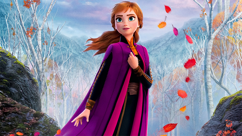 Anna stands in a forest surrounded by swirling autumn leaves. More attention has been paid to lesbian Disney characters like Elsa than bisexual Disney characters like Anna.