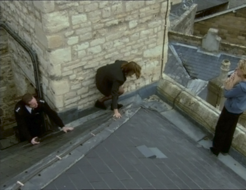 A scene from Bad Girls where Helen Stewart is knelt on a roof trying to talk to Zandra Plackett who is stood by the edge carrying her newborn baby
