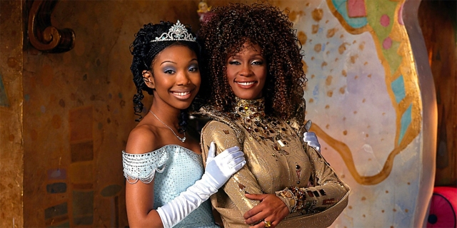 "Still from Roger and Hammersteins 1997 ""Cinderella"". shows the two stars, Brandy and Whitney Houston, Brandy is wearing a pal blue ball gown and tiara and Whitney Houston is wearing a gold gown."