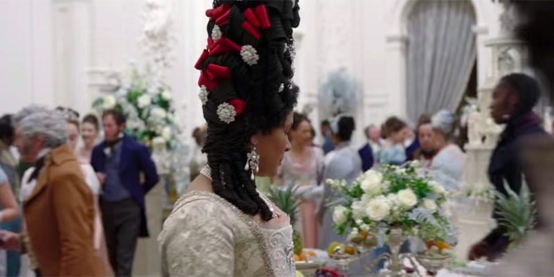 Image shows The Queen at a wedding. Her hair is in black box braids that are shaped into curls and stacked high. Red bows and pearls with diamonds adorn her hair and a braided side pony that is curled rest on her shoulder.