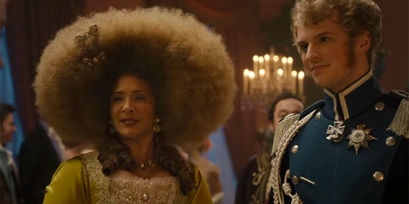 Image shows The Queen standing next to her nephew, The Prince. Her hair is a ombre black to brown and is shaped into a large and beautiful afro. It is adorned with two jeweled bows and 2 low ponytails in curls are on either side of her.