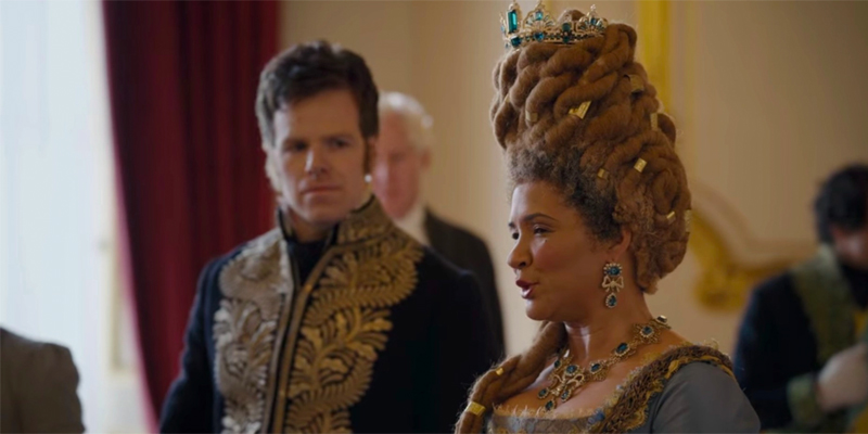Image shows The Queen at the palace in conversation. Her hair is an ombre black to brown and in dreadlocs. They are swooped and stacked high and adorned with golden jewels. A tiara rests on the top.