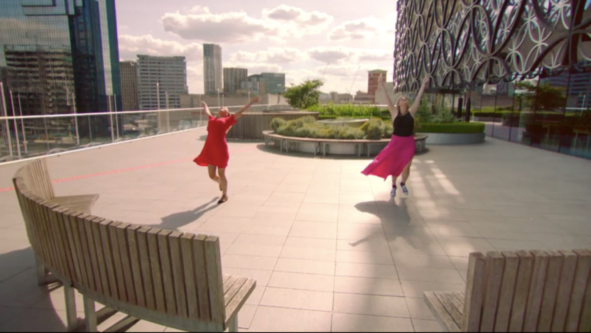 A scene from reality dating show Flirty Dancing where two girls are dancing on a rooftop in late afternoon