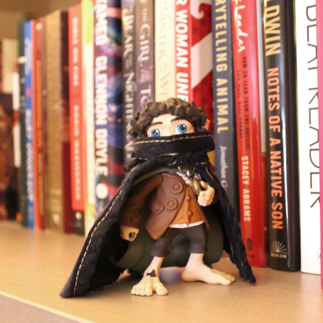 A small toy Frodo Baggins is standing on a bookshelf wearing a mask and a cap. Frodo is the Anti-Fascist on the Shelf!